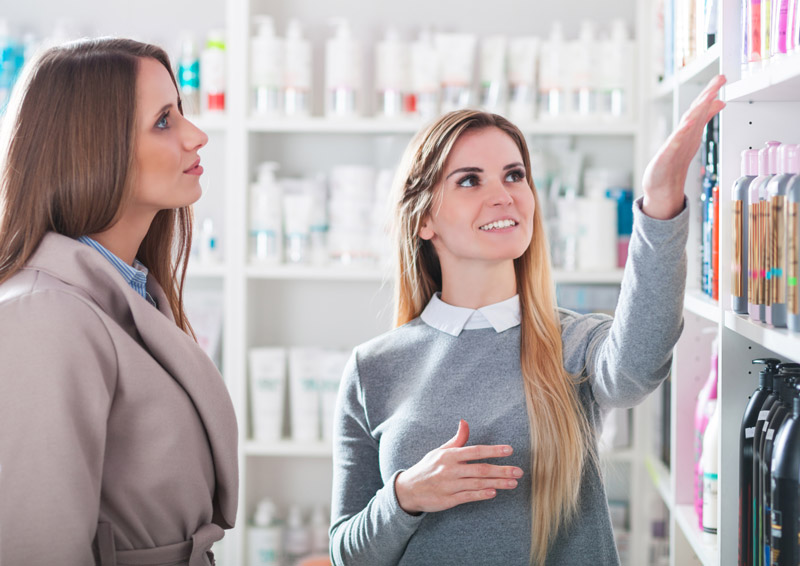 A beauty consultant helps a customer with hair product recommendations in a store