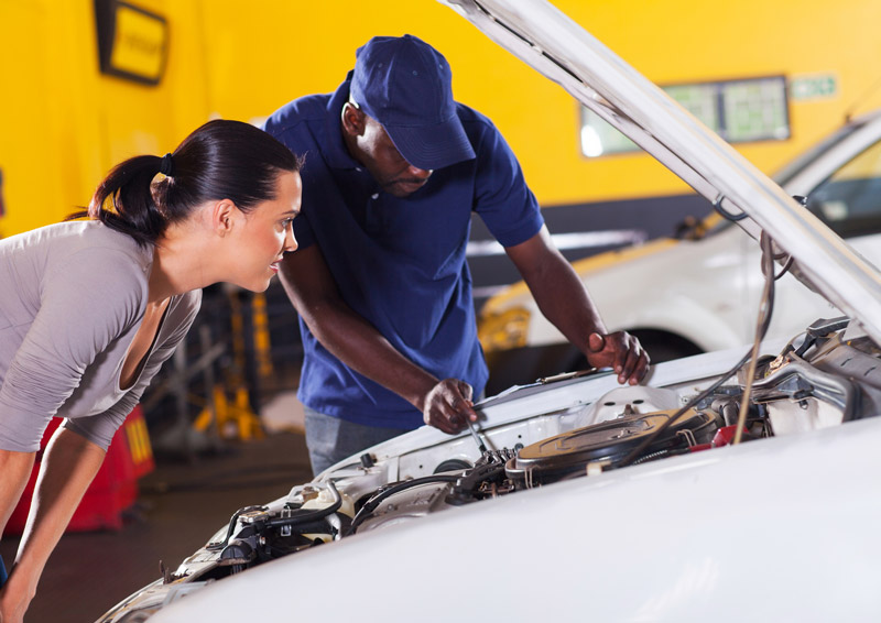 A mechanic looks under the hood of a car with a female customer in an auto service garage