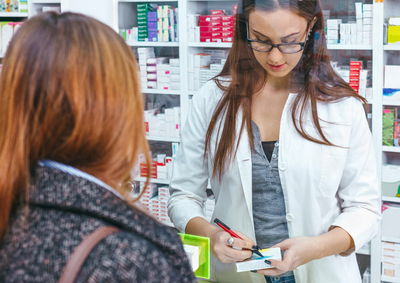 A pharmacist helps a customer with a prescription