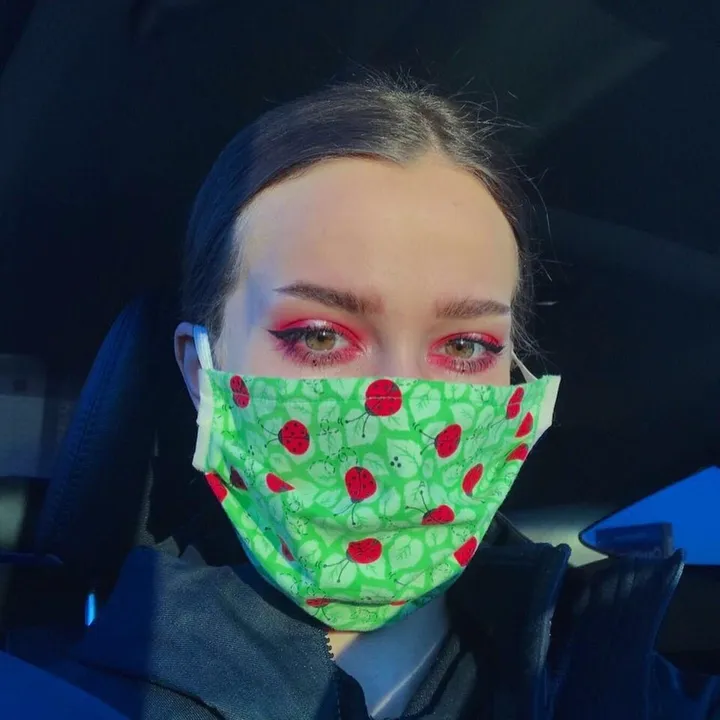 A woman wearing a facemask wears bright eye makeup