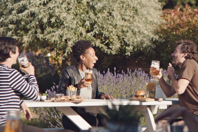 Ad for Carlsberg beer with friends at an outdoor pub social distancing