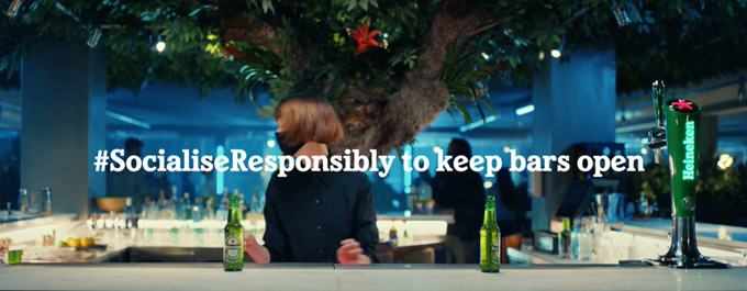Heineken beer ad showing a woman social distancing and wearing a mask in a bar