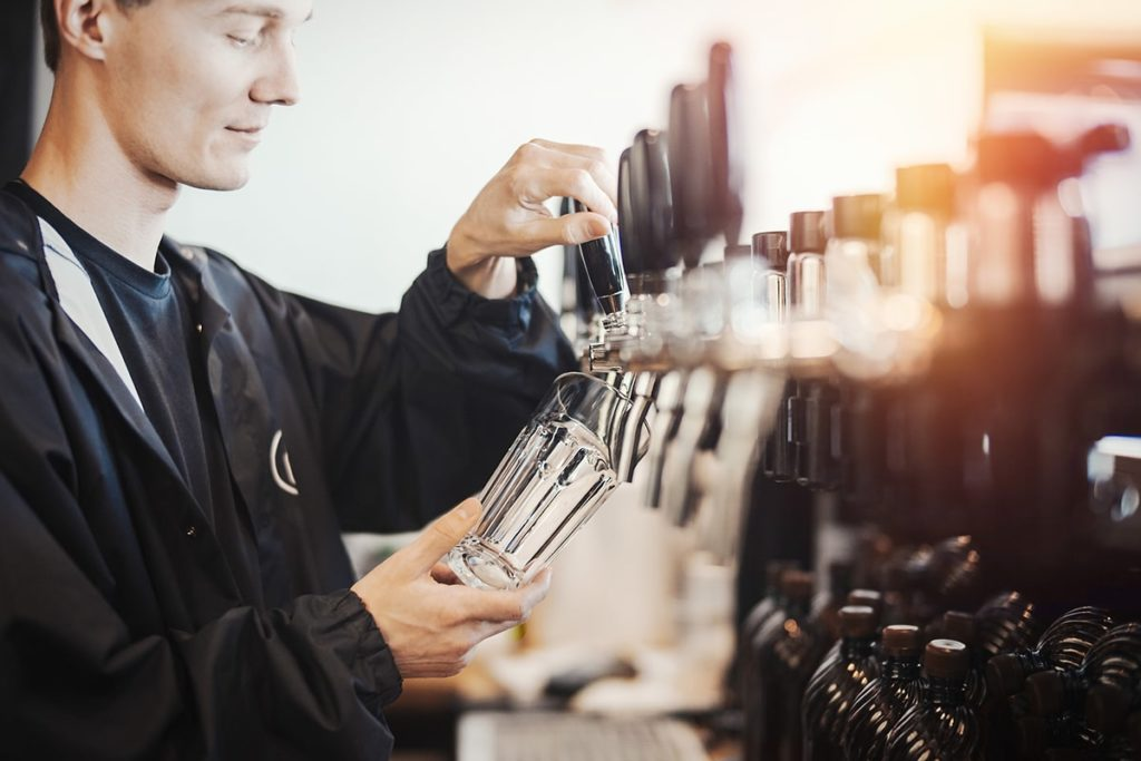 Man pouring beer in bar